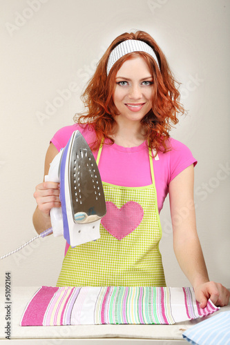 Young beautiful woman ironing clothes in room on grey