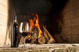 Copa de vino tino con fuego de chimenea de fondo.