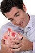 A businessman hugging his piggy bank.