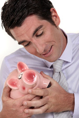 A businessman hugging his piggy bank.