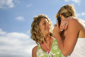 Two blond friends making a call whilst at the beach