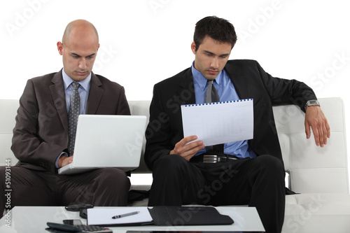 Two businessmen reading through presentation