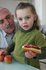 Little girl with grandfather eating sandwich