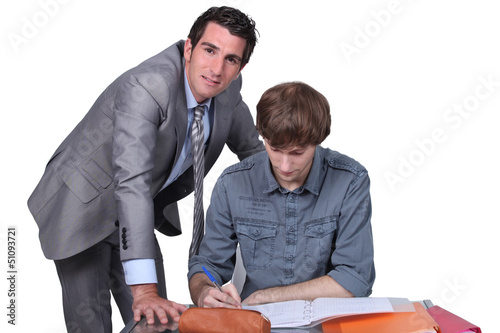 Teacher helping male teenager