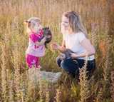 little girl and mother with cats outdoor