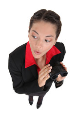 Curious businesswoman holding binoculars