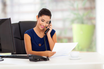 young businesswoman on the telephone and reading report