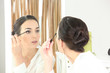 Brunette applying mascara in mirror