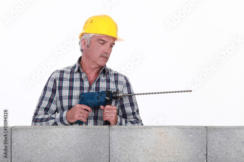 Worker with a masonry drill