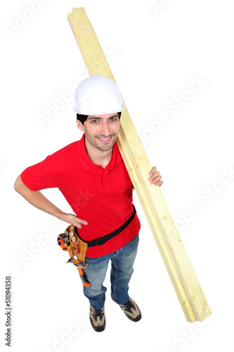 high angle shot portrait of craftsman carrying lumber
