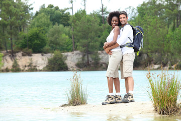 Hiking couple stood by lake