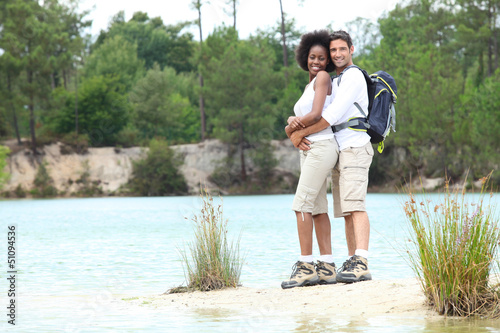 Hiking couple stood by lake