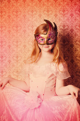 little girl in festive dress and carnival mask