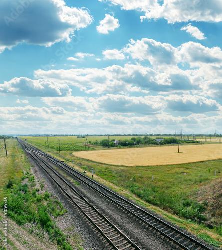 railroads to horizon and cloudy sky