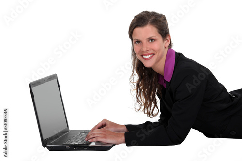 Businesswoman laying on the floor with her laptop.