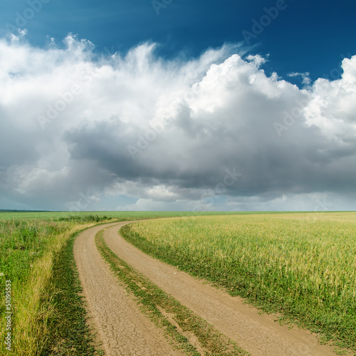 dirty road in fields and low clouds on horizon