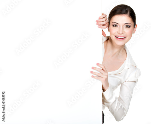 Young smiling woman looking from white blank banner