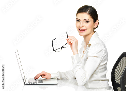 woman sits from the  table and working on laptop