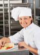 Happy Female Chef Garnishing Dish