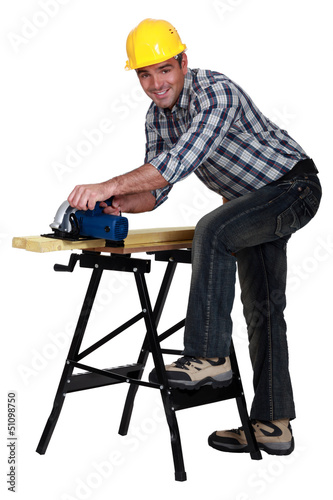 carpenter at work with sander machine isolated on white