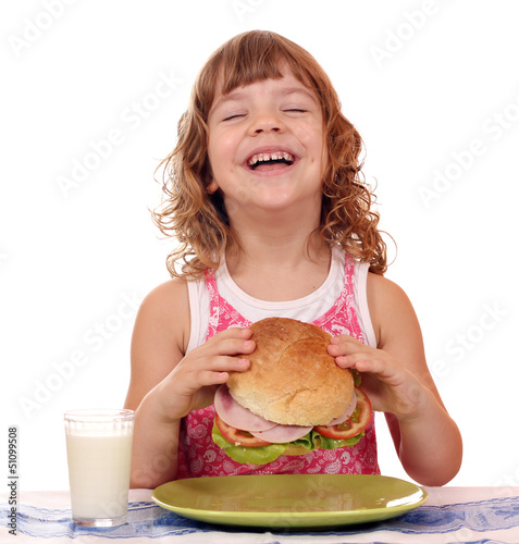 happy little girl eat big sandwich breakfast time