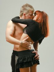 Sexy passionate young couple hugging on grey isolated background