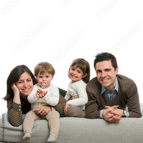 Portrait of happy family laying on couch.