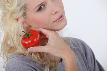 Blond woman holding tomato