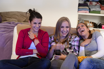 Laughing young girls watching TV together
