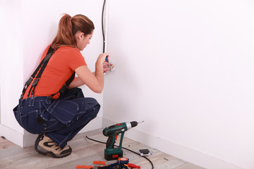 young woman installing electricity in a house