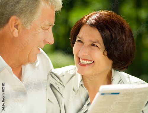 Happy senior couple reading outdoors