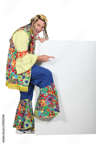 Man wearing hippy costume pointing at blank message board