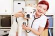 Lachende Tierärztin beim Abhören eines Hundes