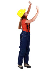 A female construction worker checking the walls.