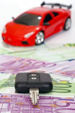 Black key on euro banknotes and red sports car background