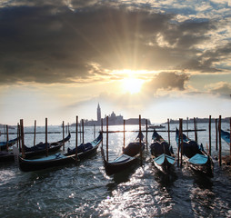 Venice with gondolas against sunset in Italy