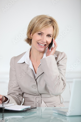 Businesswoman sat at desk holding mobile telephone