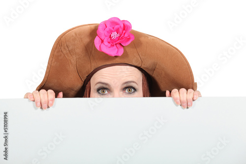 Woman hiding wearing a big brown hat
