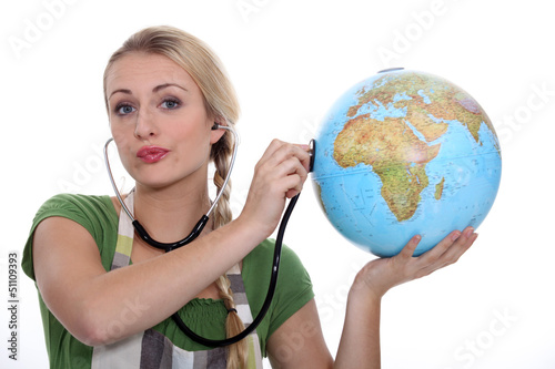 HOLDING, STETHOSCOPE  ON GLOBE