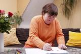 Behinderte Frau malt mit Buntstiften in einem Heft