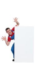 Scary builder jumping out from behind poster