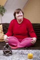 Behinderte Frau sitzt im Schneidersitz auf der Couch