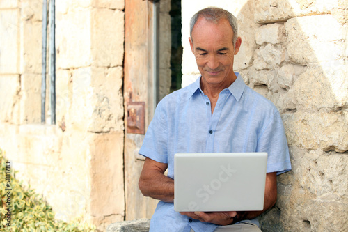 man using computer outside a lovely stone building