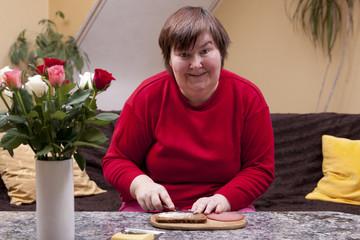 Geistig behinderte Frau macht sich ein belegtes Brot