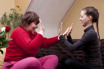 Zwei Frauen, eine davon behindert, machen Rythmusübungen