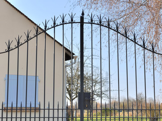 portail devant  une maison aux volets bleus