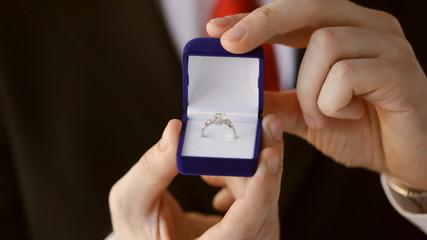 groom holding wedding ring
