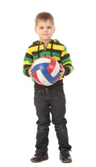 The cute little boy holds a volleyball ball and smiles