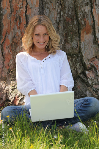 Woman on laptop under tree