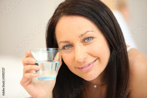 Brunette laying on bed with glass of water